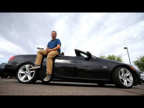 Chris Williamson poses for a photo sitting on his car in Phoenix on In this April 23. Williamson bought a BMW 3 Series convertible and covers the payments by renting it to strangers on a peer-to-peer car sharing app called Turo.