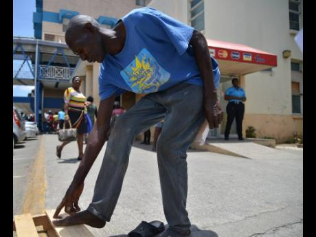 Gary Ashley, seen here outside Kingston Public Hospital yesterday, shows the Gleaner team his infected toe, for which he said he is scheduled to undergo an X-ray in one month.