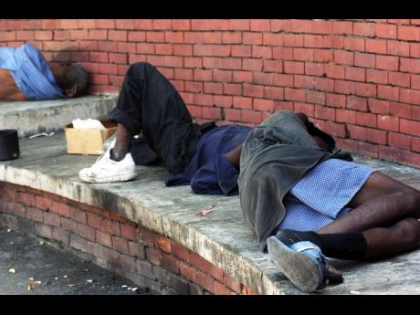 Two homeless men asleep on a platform at the Sir William Grant Park in downtown Kingston.