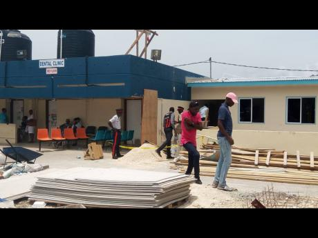 Police investigators at the construction site where a disgruntled employee opened fire on two colleagues at the Cornwall Regional Hospital in Mount Salem, St James, yesterday.