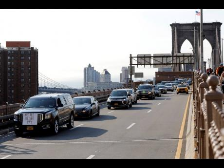 Uber and Lyft drivers, with signs on their vehicles supporting better wages, cross the Brooklyn Bridge in a caravan of about 25 vehicles, Wednesday, May 8, 2019 in New York.