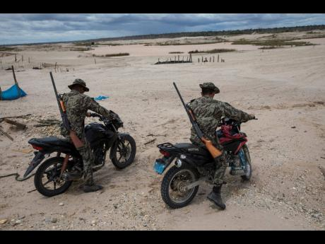 In this March 27, 2019 photo, Operation Mercury soldiers patrol on motorbikes an area once used by illegal miners in Peru's Tambopata province. Peruvian police and soldiers search for and destroy equipment used by illegal gold miners in a part of the Amazon rainforest where the mining transformed dense foliage into a desert pocked with dead trees and toxic pools.