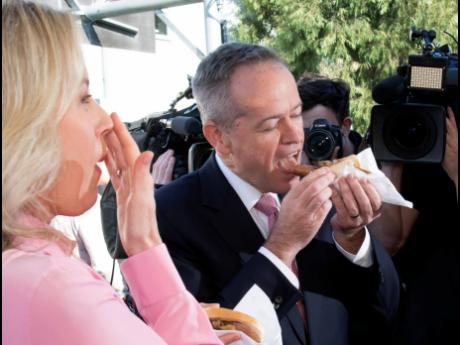 Australian opposition leader Bill Shorten and his wife Chloe eat a sausage sandwich on a federal election day in Melbourne, Australia, Saturday, May 18, 2019. Polling stations opened across Australia on Saturday in elections that are likely to deliver the nation's sixth prime minister in as many years. (AP Photo/Andy Brownbill)