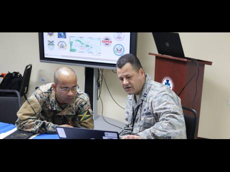 A member of the DC National Guard examines Jamaica's National Disaster Action Plan with a Jamaica Defence Force soldier, as part of a military-to-military planning exercise recently.