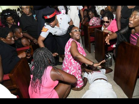 Mourners assist a person who fainted at yesterday's funeral for Shantae Skyers at Meadowvale Seventh-day Adventist Church, Chancery Street, Kingston.