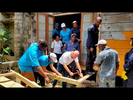 A work crew from the Royalton White Sands, Trelawny police and Rotaract Club of Falmouth repairs the ageing home of 100-year-old Boris Anderson in Martha Brae, Trelawny.