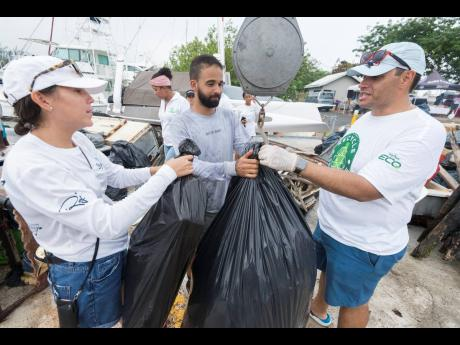 Members of Team Mama Mia, Bianca Bovell (left) and Jonathan Kerr (centre), are assisted by Nicholas McKoy in weighing in trash collected from the sea in the Trash Tournament held at the Royal Jamaica Yacht Club in Kingston on Thursday. Team Mama Mia won with a haul of 1,988 pounds of trash.
