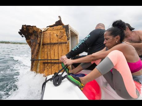 Members of Team Xanadu, owner and captain Mark Hosang (left), Michelle Laidlaw (centre) and Dean Arscott, haul in a refrigerator as they returned to the dock in the Trash Tournament held at the Royal Jamaica Yacht Club on Labour Day. Fifteen teams competed to collect the heaviest cache of trash from the sea. Gladstone Taylor/Multimedia Photo Editor