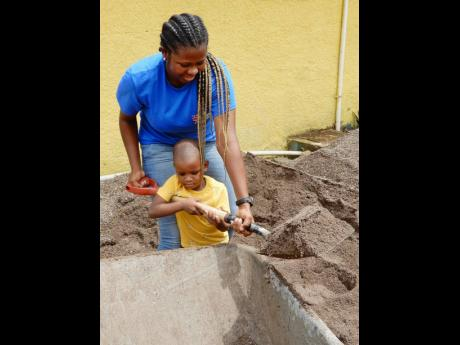 Three-year-old Aiden Meeks was adamant that he had to share his mom's (Ann-Marie Campbell) work on Labour Day at the Eltham Early Childhood Institution in St Ann. She had to relent.
