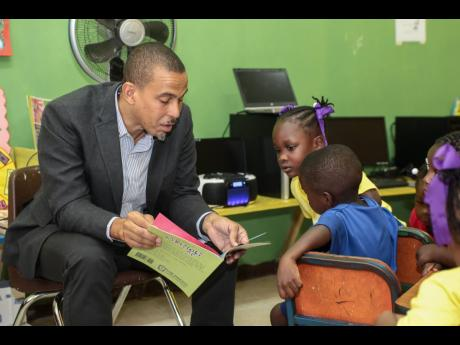 Rotary Club of New Kingston member Dr Peter Johnson reads to students at the Gordon Town Basic School in St Andrew.