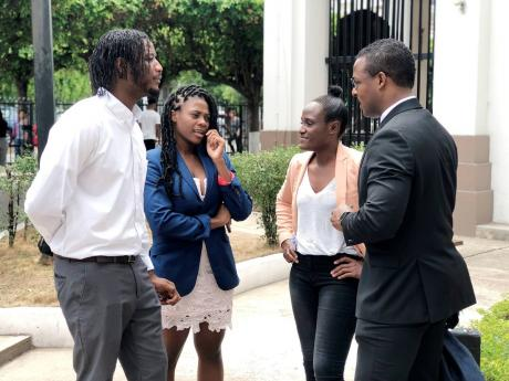 From left: Siblings of fashion designer Dexter Pottinger – Danta Aarons, Ta-Shan Adams, Lakeisha Aarons – speaking with attorney-at-law Duane Thomas outside of the Supreme Court in downtown Kingston yesterday.