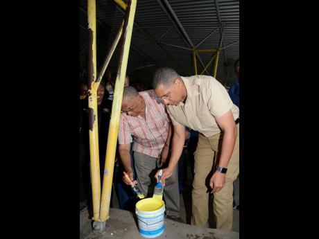 Prime Minister Andrew Holness (right) and Opposition Leader Dr Peter Phillips help to paint a section of Papine High School at one of the four National Labour Day Projects on Thursday.