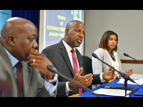 Planning Institute of Jamaica (PIOJ) Director General Dr Wayne Henry (centre) responds to questions during Wednesday's (May 22) quarterly briefing at the PIOJ's head office in New Kingston. Listening are senior director for the institute's Economic Planning, Research and Policy Logistics Division, James Stewart; and programme director for the Vision 2030 Jamaica Secretariat at the PIOJ, Elizabeth Emanuel.