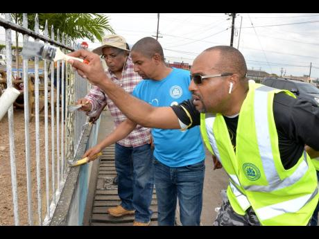 Mayor of Kingston Delroy Williams (centre) is joined by Member of Parliament for Western St Andrew Anthony Hylton (left) and chief executive officer for the Kingston and St Andrew Municipal Corporation, Robert Hill, in painting the fence of a community park on Spanish Town Road, St Andrew, on Labour Day.