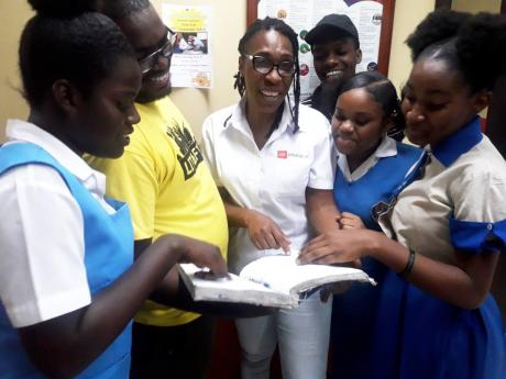 AT LEFT: Outreach officer at the Teen Hub, Jerome Edwards (second left), and Centre Manager Nicola Walker (third left) engage students at the Half-Way Tree facility in St Andrew.