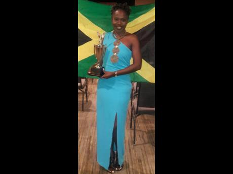 Faith Ellis displaying the trophy she won for being adjudged the Caribbean Champion of Public Speaking at the Toastmasters International District 81 Annual Conference in Bonaire, the Caribbean part of the Netherlands, recently.