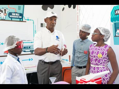 Livingston Binns, sales and marketing manager at Island Dairies, explains the process of testing milk for bacteria to students of Monsignor Colin Bryan Preparatory School.