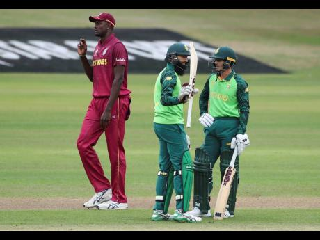 West Indies captain Jason Holder (left) walks past South Africa's Hashim Amla (centre) raising his bat to celebrate scoring 50 runs during their Cricket World Cup warm-up match in Bristol, England, yesterday. On the right is South Africa's Quinton de Kock.