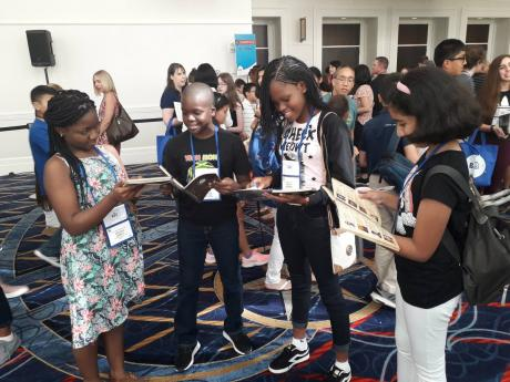 READY FOR THE SPELLDOWN Darian Douglas (second left), The Gleaner's Children's Own Spelling Bee champion, and fellow finalists (from left) Ashleigh Jarrett, Rhonoya Anderson and Honey Advani review reading material during an interactive session ahead of today's start of the Scripps National Spelling Bee competition in the United States.
