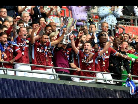 Aston Villa's Jack Grealish (centre left) and James Chester (centre right) celebrate with the trophy after winning the English Championship Play-off final between Aston Villa and Derby County at Wembley Stadium, London, yesterday.
