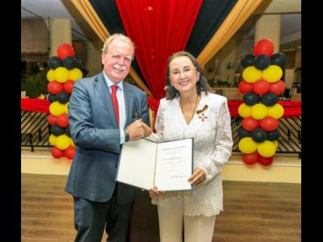 Karolin Troubetzkoy receives the Order of Merit from His Excellency Holger Michael, ambassador of the Federal Republic of Germany to the Caribbean.