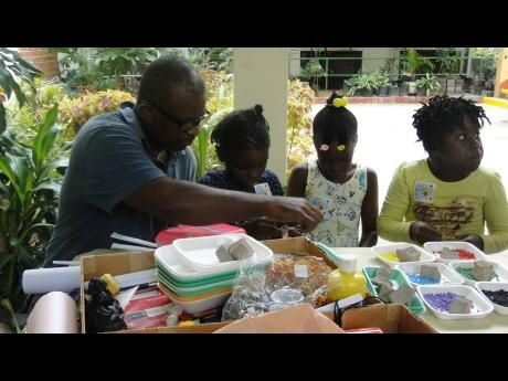 Valentine 'Koda' McLean teaching some youngsters to make jewellery.
