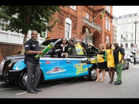 Jamaica Tourist Board UK staff pose with one of the wrapped taxis.