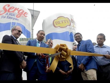 Prime Minister Andrew Holness cuts the ribbon signifying the official launch of the consolidated Serge Island Dairies plant at Bogwalk, St Catherine on Tuesday, May 28. The prime minister is flanked by (from left in the foreground), Chairman of Seprod Paul Scott,  Seprod CEO Richard Pandohie, and Opposition spokesman Noel Arscott. Minister of Industry, Commerce, Agriculture and Fisheries Audley Shaw is partially seen in the background.