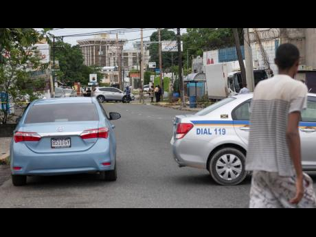 A man walks by the cordoned-off section of Old Hope Road yesterday as members of the Jamaica Constabulary Force process a crime scene where a man was shot dead.