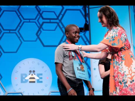 Eleven-year-old Jamaican speller Darian  Douglas of Glenmuir High School is awarded his medal after being named among the finalists in the 2019 Scripps National Spelling Bee yesterday. There are 565 spellers in this year's competition, ranging in age from seven to 15. The finals will take place today.