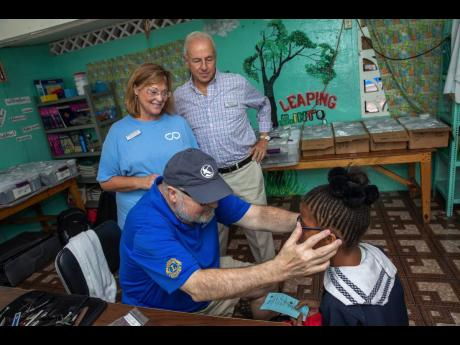 Diane Pollard, president and CEO of the Issa Trust Foundation, and Chairman Paul Issa smile as a volunteer fits a pair of glasses on a Savanna-La-Mar Primary School student.
