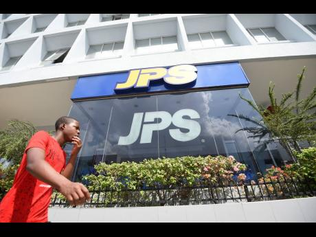 A man walks by the Jamaica Public Service building in New Kingston on Tuesday, May 7.