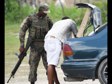 A soldier conducts a search of a vehicle at a checkpoint in Whitehouse, Westmoreland, which is one of three parishes, including Hanover and St James, under a state of public emergency. The security measure restricts personal freedom and grants extraordinary powers to soldiers and the police.