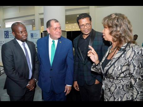Diane Edwards (right), president of JAMPRO, has the rapt attention of (from left) Ian Mitchell, director of the Trinidad and Tobago Manufacturers' Association; Audley Shaw, minister of industry, commerce, agriculture and fisheries; and Richard Pandohie, CEO of Seprod, at yesterday's official opening of the Jamaica International Exhibition at the Montego Bay Convention Centre in St James.