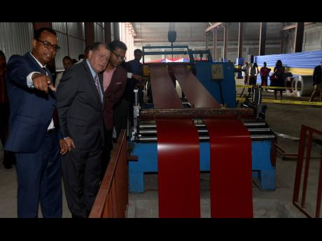 Lionel Rookwood/Photographer  Executive Chairman of Arc Manufacturing Limited Norman Horne (left) explains the process of metal slitting to Minister of Industry, Commerce, Agriculture and Fisheries Audley Shaw (second left) and JMEA Deputy President Richard Pandohie during the official commissioning of the plant at Arc Manufacturing in Kingston on May 29.