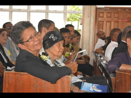 Mrs. Novelette Tai listens attentively to tributes paid to her late husband, Aston. Beside her is Tai's sister, Cynthia.