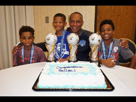 Coach André Virtue (second right) shares lens time with Ballaz players (from left) Isaiah Stiebel (under-12), DeJan Ho-Young (under-9) and Kai Myles (under-11) as they celebrate their triple victory at the recent Williamsburg Invitational Soccer Tournament.