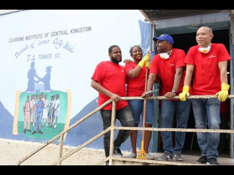 Nationwide News Reporter William Mitchell (left) takes a breather from painting inside The Learning Institute of Central Kingston, a Grace & Staff Community Development Foundation homework centre. Along with him are (from left) Tanketa Chance-Wilson, the foundation's general manager; Steven Whittingham, managing director of GK Insurance; and Andrew Leo-Rhynie, managing director of GK Capital Management.