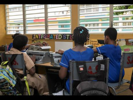 Students operate Perkins Braillers – a braille code typewriter – in a classroom at the Salvation Army School for the Blind on Mannings Hill Road in St Andrew last Friday.