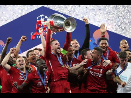 Liverpool's Jordan Henderson lifts the trophy to celebrate with his teammates winning the Champions League final match between Tottenham Hotspur and Liverpool at the Wanda Metropolitano Stadium in Madrid, yesterday. Liverpool won 2-0.