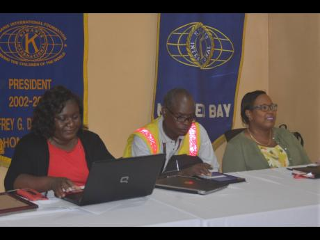 Kenute Hare (centre), director of the Road Safety Unit in the Ministry of Transport and Mining, sits at the head table during Thursday's meeting of the Kiwanis Club of Montego Bay at Martina's Juice Bar and Grill on Howard Cooke Boulevard in the western city. Also pictured are Camille Barrett (right), president of the Kiwanis Club of Montego Bay, and club secretary Carlene Moore.