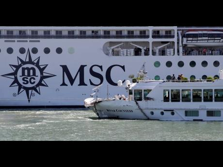 The MSC Magnifica cruise ship passes by the tourist boat, foreground, bottom right, that was struck by a towering cruiser, foreground right, in Venice, Italy, Sunday, June 2, 2019. The MSC Opera cruise ship has struck a dock and a tourist river boat on a busy canal in Venice.
