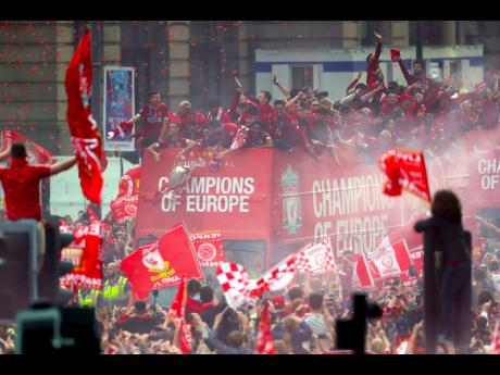 Fans look on as Liverpool FC captain Jordan Henderson dangles the UEFA Champions League trophy from an open top bus during the team's Winners Parade through the streets of Liverpool, England, yesterday.