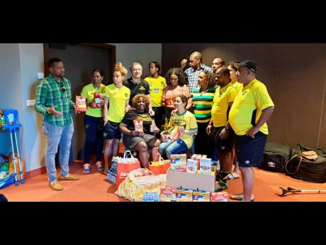 Jamaica's senior women's football team and head coach Hue Menzies (right) receive home comforts from members of the Jamaica Association in Switzerland in Lyon, France, yesterday.