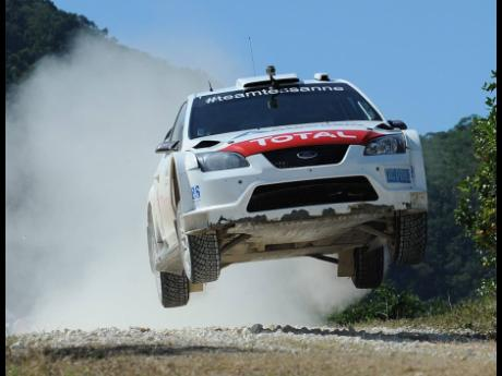 Jamaican rally driver Jeffrey Panton and co-driver Mike Fennell Jr aboard their Ford Focus WRC rally car during a local rally in Wakefield, St Catherine, on Sunday, December 1, 2013.