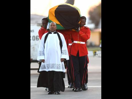 Lt Col Denston Smalling, chaplain of the Jamaica Defence Force, leads members of the 1st Batallion Jamaica Regiment as they carry the coffin bearing the remains of former Prime Minister Edward Seaga, which arrived at Norman Manley International Airport yesterday evening. Seaga, 89, passed away last week at a Florida hospital in the United States.