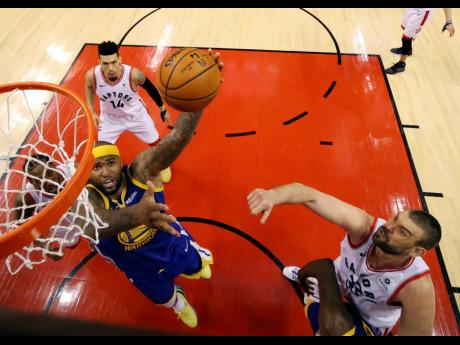 Golden State Warriors' DeMarcus Cousins (bottom left) drives against Toronto Raptors' Marc Gasol (right) and  Danny Green (top left) during Game 2 of the NBA Finals, in Toronto, Canada on Sunday.