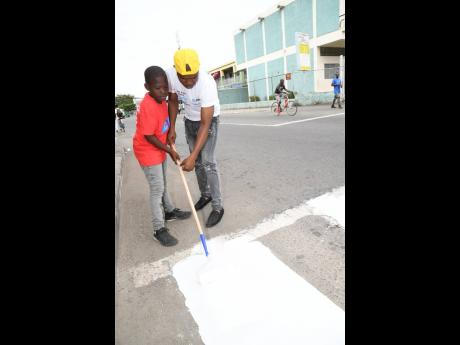 Jahmar Rose assists his son, Daniel, to paint a pedestrian crossing on the Gordon Town main road in St Andrew on Labour Day.