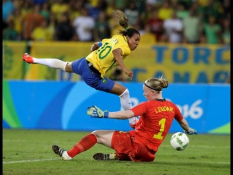 In this August 6, 2016, file photo, Brazil's Marta (left) leaps over Sweden goalkeeper Hedvig Lindahl as she attempts a shot on goal during the Olympic football tournament in Rio De Janeiro, Brazil.