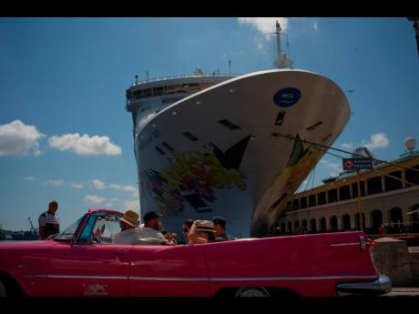 Tourists who have just disembarked from a cruise liner, tour the city aboard a vintage American convertible, in Havana, Cuba, Tuesday, June 4, 2019.